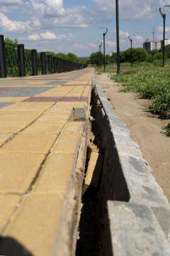 Испытания июньским ливнем не прошел тротуар. Из-за отсутствия ливневок вода вымыла песок, плитки снова разъехались в разные стороны.На газоне лебеда Комфортная городская среда благоустройство