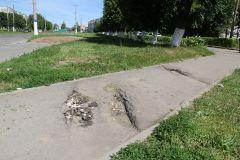 Следы на тротуаре — здесь проехала тяжелая техника.Про траву и тротуар благоустройство