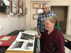 Семья Николаевых рассматривает фотографии в альбоме по истории города.Спасибо за цветущий город! Первостроители